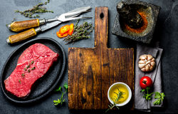 Fresh raw meat steak beef tenderloin, herbs and spices around cutting board. Food cooking background with copy space.  Royalty Free Stock Photos