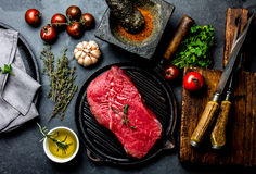Fresh raw meat steak beef tenderloin, herbs and spices around cutting board. Food cooking background with copy space Royalty Free Stock Photo
