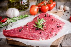 Fresh raw meat steak on a cutting board with rosemary and pepper. Raw meat steak on a cutting board with rosemary and pepper on rustic background Royalty Free Stock Photo