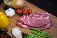 Fresh raw meat steak with spice and vegetables on wood surface. Fresh raw meat steak with green beans, spice, tomatoes, garlic and onion on wood surface Stock Image