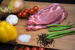 Fresh raw meat steak with spice and vegetables on wood surface. Fresh raw meat steak with green beans, spice, tomatoes, garlic and onion on wood surface Stock Photography