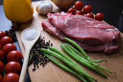 Fresh raw meat steak with spice and vegetables on wood surface. Fresh raw meat steak with green beans, spice, tomatoes, garlic and onion on wood surface Royalty Free Stock Photography