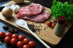 Fresh raw meat steak with spice and vegetables on wood surface. Fresh raw meat steak with spice, tomatoes, garlic and onion on wood surface Stock Photo