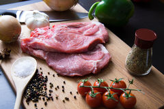 Fresh raw meat steak with spice and vegetables on wood surface. Fresh raw meat steak with spice, tomatoes, garlic and onion on wood surface Stock Images