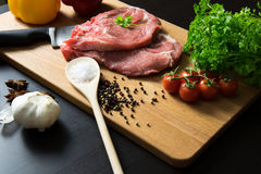 Fresh raw meat steak with spice and vegetables on wood surface. Fresh raw meat steak with spice, tomatoes, garlic and onion on wood surface Royalty Free Stock Photos