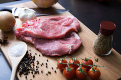 Fresh raw meat steak with spice and vegetables on wood surface. Fresh raw meat steak with spice, tomatoes, garlic and onion on wood surface Royalty Free Stock Images