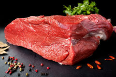 Fresh and raw meat. Still life of red meat steak ready to cook on the barbecue. Black slate background Royalty Free Stock Photography
