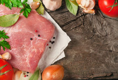 Fresh and raw meat with tomatoes and greens closeup. Fresh and raw meat with tomatoes and greens close-up on natural wooden background. Top view with copy space Stock Image