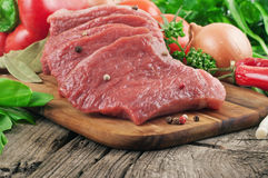 Fresh raw meat with vegetables. On old wooden table closeup Stock Photo