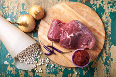 Fresh raw meat, white bean and vegetables on an old wooden table Stock Photos