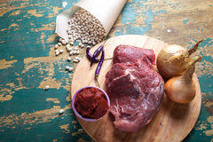 Fresh raw meat, white bean and vegetables on an old wooden table. Ingredients for traditional turkish meal - Kuru fasulye Royalty Free Stock Photo