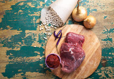 Fresh raw meat, white bean and vegetables on an old wooden table Stock Photo