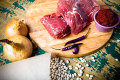Fresh raw meat, white bean and vegetables on an old wooden table. Ingredients for traditional turkish meal - Kuru fasulye. Toned Royalty Free Stock Photography