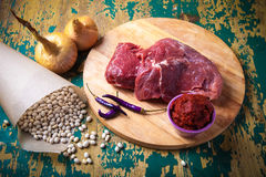 Fresh raw meat, white bean and vegetables on an old wooden table. Ingredients for traditional turkish meal - Kuru fasulye. Toned Royalty Free Stock Photos