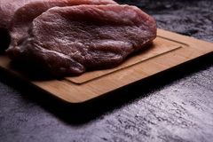 Fresh raw meat on wooden board backlit. On black wooden background. Gourmet food and fresh uncooked meal Stock Photography