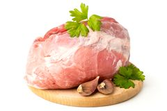 Fresh raw meat on wooden butcher. Fresh raw meat on wooden butcher with leaves of parsley and garlic, on a white background Royalty Free Stock Photography