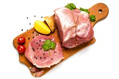 Fresh raw meat on wooden butcher with tomatoes, greens, potatoes. On white background, top view Stock Photo