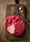 Fresh raw meat on wooden cutting board. Fresh raw meat on old wooden cutting board Royalty Free Stock Image
