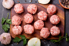 Fresh raw meatballs with vegetables. On dark table Stock Image