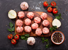 Fresh raw meatballs with vegetables. On dark table Stock Photo