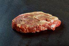 Fresh and raw meat. Whole piece of red meat ready to cook on the grill or BBQ . Background black blackboard. Fresh and raw medallions steaks Fresh and raw meat Stock Image