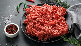 Fresh Raw mince, Minced beef, ground meat with herbs and spices on black plate royalty free stock photo