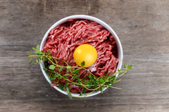 Fresh raw minced beef with egg on wooden table. Fresh raw minced beef with egg on wooden table Stock Image