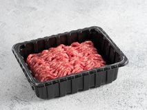 Raw minced beef on light gray cement background. Fresh raw minced beef in plastic tray over light gray cement background with copy space Stock Images