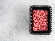 Raw minced beef on light gray cement background. Fresh raw minced beef in plastic tray over light gray cement background with copy space. Top view or flat-lay Royalty Free Stock Photos