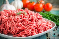 Fresh raw minced beef in a plate close up. On a rustic wooden table Stock Photo