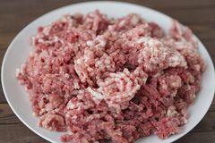 Fresh raw minced beef and pork. In a plate close up on a rustic wooden table Stock Photo