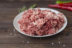 Fresh raw minced beef and pork. In a plate close up on a rustic wooden table Stock Photos