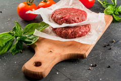 Fresh raw minced beef steak burger. Fresh raw home-made minced beef steak burger with spices, basil and tomatoes on a cutting board on a stone table, copy space Royalty Free Stock Photo