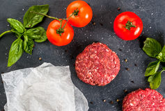 Fresh raw minced beef steak burger. Fresh raw home-made minced beef steak burger with spices, basil and tomatoes on a cutting board on a stone table, copy space Stock Image