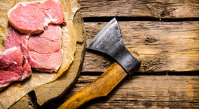 Fresh raw minced meat with an axe. Royalty Free Stock Images