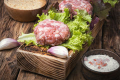 Fresh raw minced meat beef. Raw minced meat and lettuce on rustic wooden background Royalty Free Stock Photos