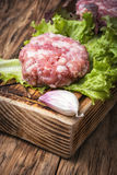 Fresh raw minced meat beef. Raw minced meat and lettuce on rustic wooden background Royalty Free Stock Photo