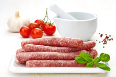 Fresh raw minced meat sausages. On white plate Royalty Free Stock Images