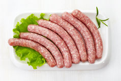 Fresh raw minced meat sausages. On white plate Stock Image
