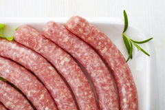 Fresh raw minced meat sausages. On white plate Royalty Free Stock Photography