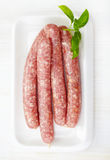 Fresh raw minced meat sausages. On white plate Stock Photo