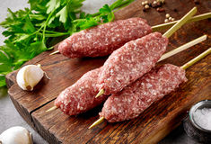 Fresh raw minced meat skewers kebabs. On wooden cutting board Royalty Free Stock Photos
