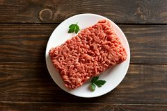 Fresh raw minced meat. On white plate over wooden background with copy space. Top view, flat lay Royalty Free Stock Image