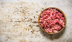 Fresh raw minced meat in a wooden bowl. On rustic background. Free space for text . Top view Stock Photo