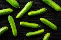 Fresh raw mini cucumber on black wood. Fresh mini cucumbers flatlay on black wood background Stock Image