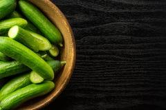Fresh raw mini cucumber on black wood. Fresh mini cucumbers in a wooden bowl flatlay on black wood background Stock Photography