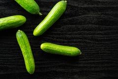 Fresh raw mini cucumber on black wood. Five fresh mini cucumbers flatlay on black wood background Stock Photos