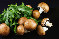 Fresh raw mushrooms brown champignons and green arugula on a dar Stock Photo