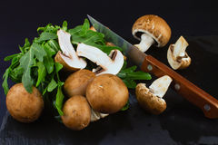 Fresh raw mushrooms brown champignons and green arugula on a dar Stock Image