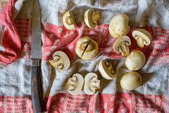Fresh raw mushrooms on cloth with nkife. Close up fresh mushrooms cut in halves and old knife lying on cloth for abstract background Stock Photo